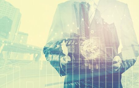 small world: Double exposure of success businessman using digital tablet with forex graph on city landscape background with the small world (Elements of this image furnished by NASA)