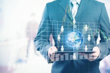 small world: Business man holding tablet pc with businesspeople icons around the small world with forex graph (Elements of this image furnished by NASA)