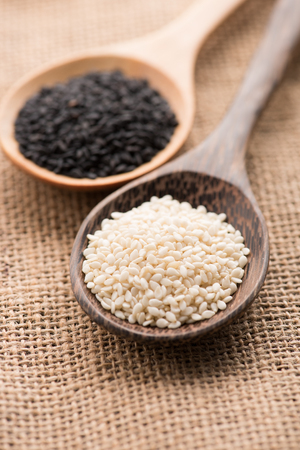 White sesame and black sesame seed on wooden spoon Imagens