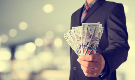 Businessman with money in hand, US dollar (USD) bills - investment, success and profitable business concepts