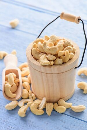 raw cashew nuts in wood bucket on blue wood table