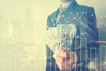 profitable: Double exposure of Businessman with money in hand with cityscape blurred building background, US dollar (USD) bills - investment, success and profitable business concepts