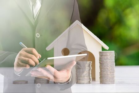 businessman using digital tablet with stacking coins and house model ,Business Finance and Money concept,Investment concept.double exposure style.