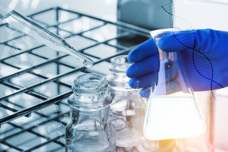 Flask in scientist hand with dropping chemical liquid to test tubes, science and medical research and development concept,science background Stock Photo