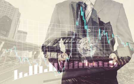 small world: Double exposure of success businessman using digital tablet with city landscape background with the small world and forex graph. (Elements of this image furnished by NASA) Stock Photo