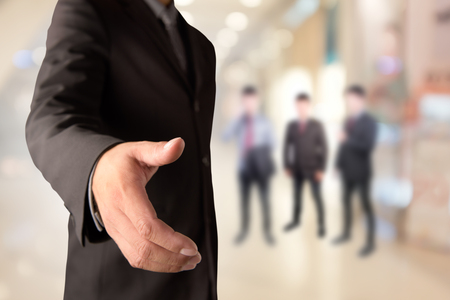 bridging the gap: Businessman offering for handshake on office buildings blur background Stock Photo