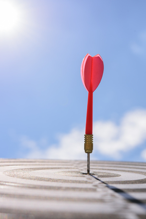 Red dart arrow hitting in the target center of dartboard with blue sky background