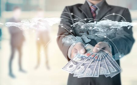 Money in Businessman hand and worldmap connection background, US dollar,investment, success and profitable business concepts.Elements of this image furnished by NASA.