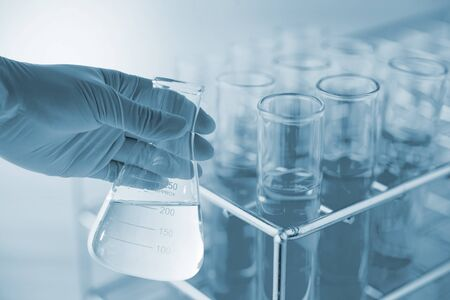 Flask in scientist hand with dropping chemical liquid to test tubes, science and medical research and development concept