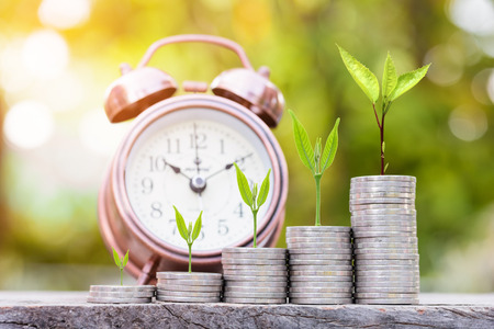 Close up of stacking gold coins with green bokeh background ,Business Finance and Money concept,Save money for prepare in the future.tree growing on coin
