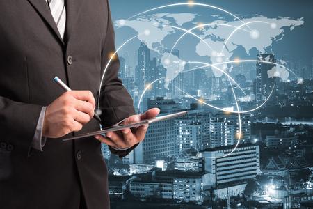 二重露光のビジネスマンは、世界地図上夜市景観背景とネットワーク回線上でタブレット PC を保持します。財務・事業コンセプト
