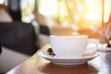 Cup of on the table, coffee shop background, warm tone
