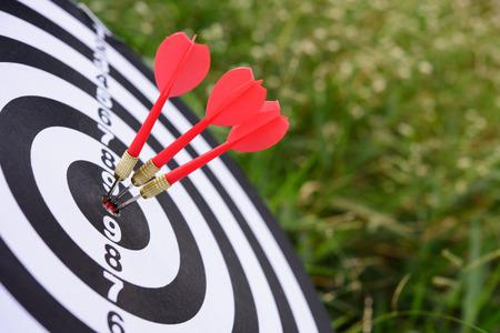 Freccia rossa freccette che colpisce nel centro del bersaglio del dartboard Archivio Fotografico - 85348297