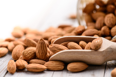The plant texture, close-up of almonds nuts on the wooden table