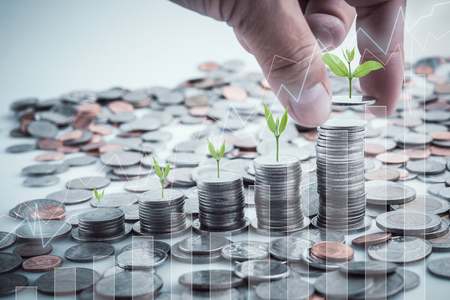 Male hand putting coins with money stack step growing growth saving money. Concept finance business investment. Tree growing on coin