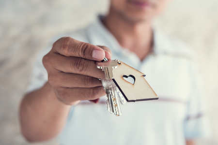 hand hold key and house model in saving plan for residence of people in society, purchasing home for living of dream of community lives. Stock Photo