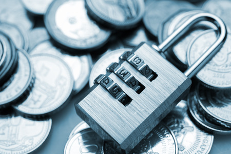 combination padlock with coin money for financial security concept Stock Photo