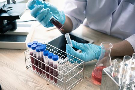 técnico de saúde com tubos de sangue no laboratório clínico para o conceito de pesquisa e desenvolvimento analítico, médico, farmacêutico e científico. Foto de archivo