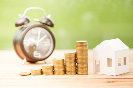 Close up of stacking money coins and home model, the saving with growing your money to real estate owner in the future concept. Stock Photo