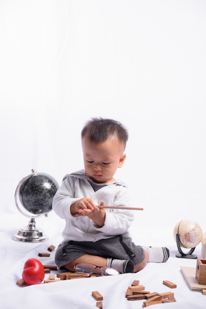 Asian Cute Boy Playing with the Globe model simulation.