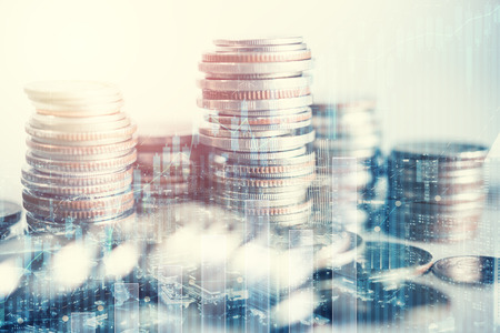 Double exposure of city and rows of coins with business graph for finance and banking concept