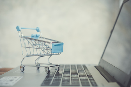 Online shopping concept. Shopping cart with laptop on the desk.