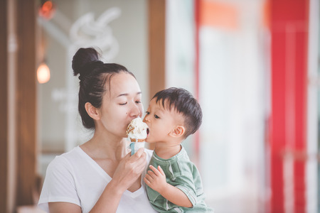Mom and kids are eating ice cream.Good relations of parent and child. Happy moments together. Stockfoto