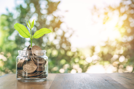 Geld im Glas auf Holztisch. Das Konzept, Geld für die Zukunft zu sparen. Finanzielle Geldkonzepte und Ersparnisse.