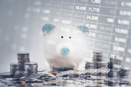 Double exposure of graph, stock display and raw of coins with piggy bank.save and investment concept.