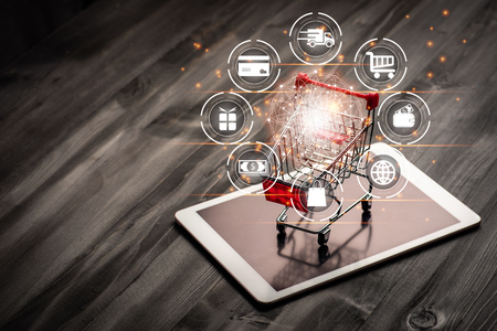 shopping trolley on tablet with darkwood background with virtual screen icon shopping online and some copy space,shopping online concept.