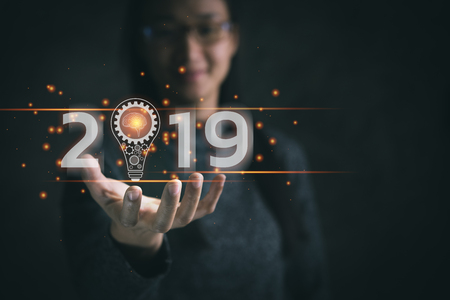 Business new year 2019. Businesswoman holding light bulb with icon business marketing and brain structure, innovative and software development, IoT concept. Trend, global networking and data exchange Stock Photo