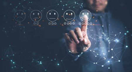 Homme d'affaires appuyant sur l'émoticône du visage souriant sur l'écran tactile virtuel. Concept d'évaluation du service client.