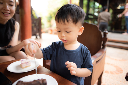 Children are eating cakes by themselves. With a mother sitting beside him