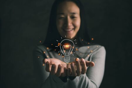 woman smiling holding icon light bulb,idea concept,Presenting new ideas. Imagens
