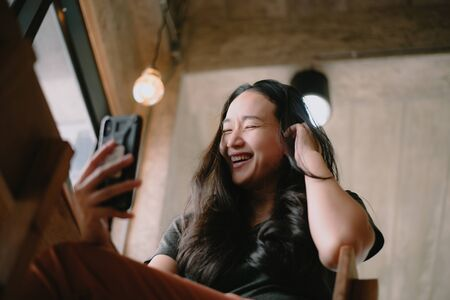 Happy smiling Asian woman holds mobile phone, close up focus on female hands and device. Customer buying goods via internet, friends chatting online, generation addicted with gadgets concept
