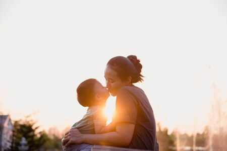 Mother and child are kissing in the park at sunset.Happy family. Imagens
