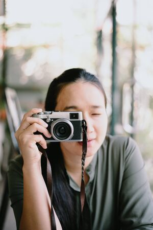 Young woman with camera.Trendy blogger use the camera in coffee shop.happy asian woman photographer holding retro fil. Banco de Imagens