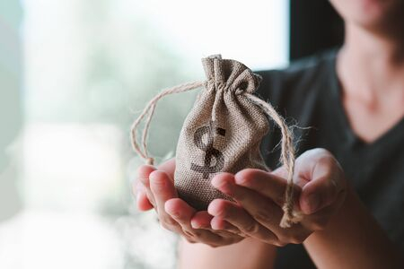 Women hand hold a money bag, a loan or saving money for future investment concept. Imagens