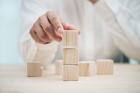 Hand arranging three wood cube stacking. Business concept growth success,hand stack woods block step on table. business development concept.copy space.