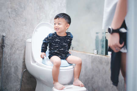 baby are training to sit in the toilet.