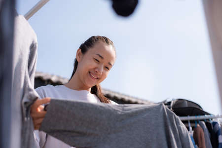 Beautiful Thai girl is drying clothes.housewife doing housework concept.