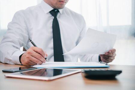 homme d'affaires ou gestionnaire professionnel comptable travaillant avec un document financier. Comptable signant le rapport financier. Analyse budget de travail comptabilité démarrage économie homme concept