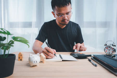 Businessman using calculators and notebooks to plan home payment installments.The concept of home installments, reducing principal and reducing interest.Asian man planning financial.