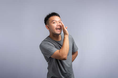 Asian man whispering. a good-looking Asian man is wearing a gray shirt.he is whispering. Banque d'images
