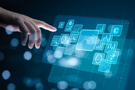 Big data analytics and business intelligence concept with chart and graph icons on a digital screen interface and a businessman hand in background