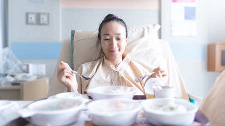 Asian woman lying on the hospital bed for admitting and she is ating breakfast. Hospitalization concept.