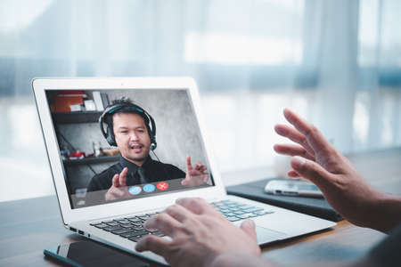 Asian business man making FaceTime video calling using online meeting via laptop computer at home office. concept of work from home teleconference and video conference. Stock Photo