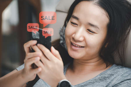 young smart asian female using smartphone with popup text sale and promotion. shopping online concept.