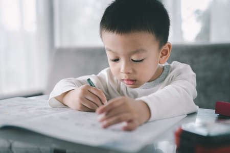 Asian Boy Doing homework with the intention. Child boy holding pencil writing, A boy drawing on white paper at the table,Elementary school and home schooling, Distance Education concept. 免版税图像
