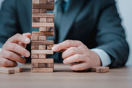 Planning, risk and strategy in business. Businessman holds the model of business, made from wood blocks. Alternative risk concept, business plan and business strategy. Insurance concept.